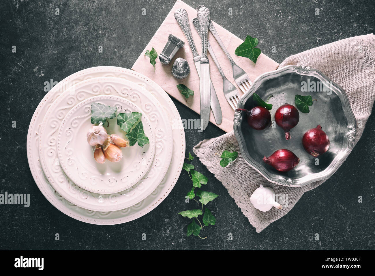 Cutlery set with plates and vegetables on gray background - Stock Image