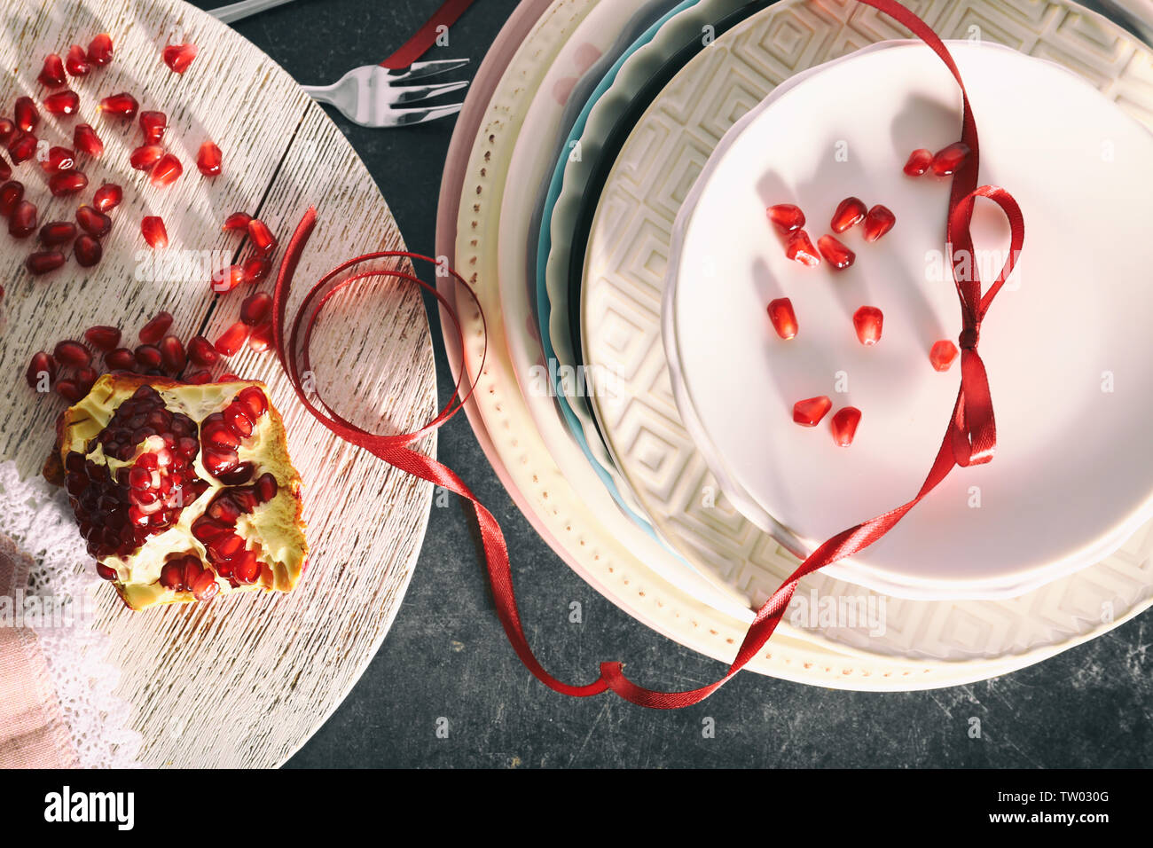 Plates and pomegranate on table - Stock Image