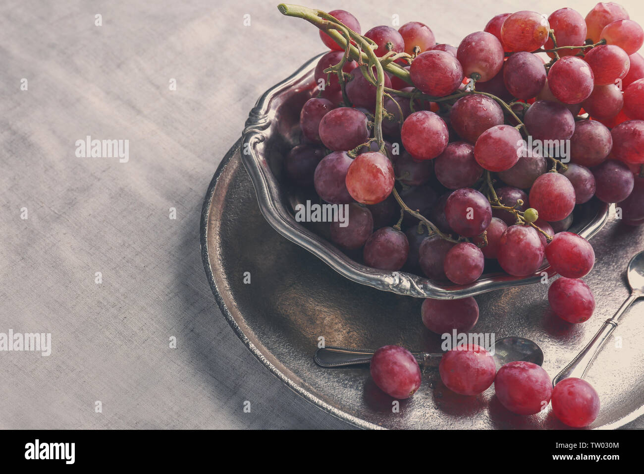 Cutlery set with plate and grapes, on linen tablecloth - Stock Image