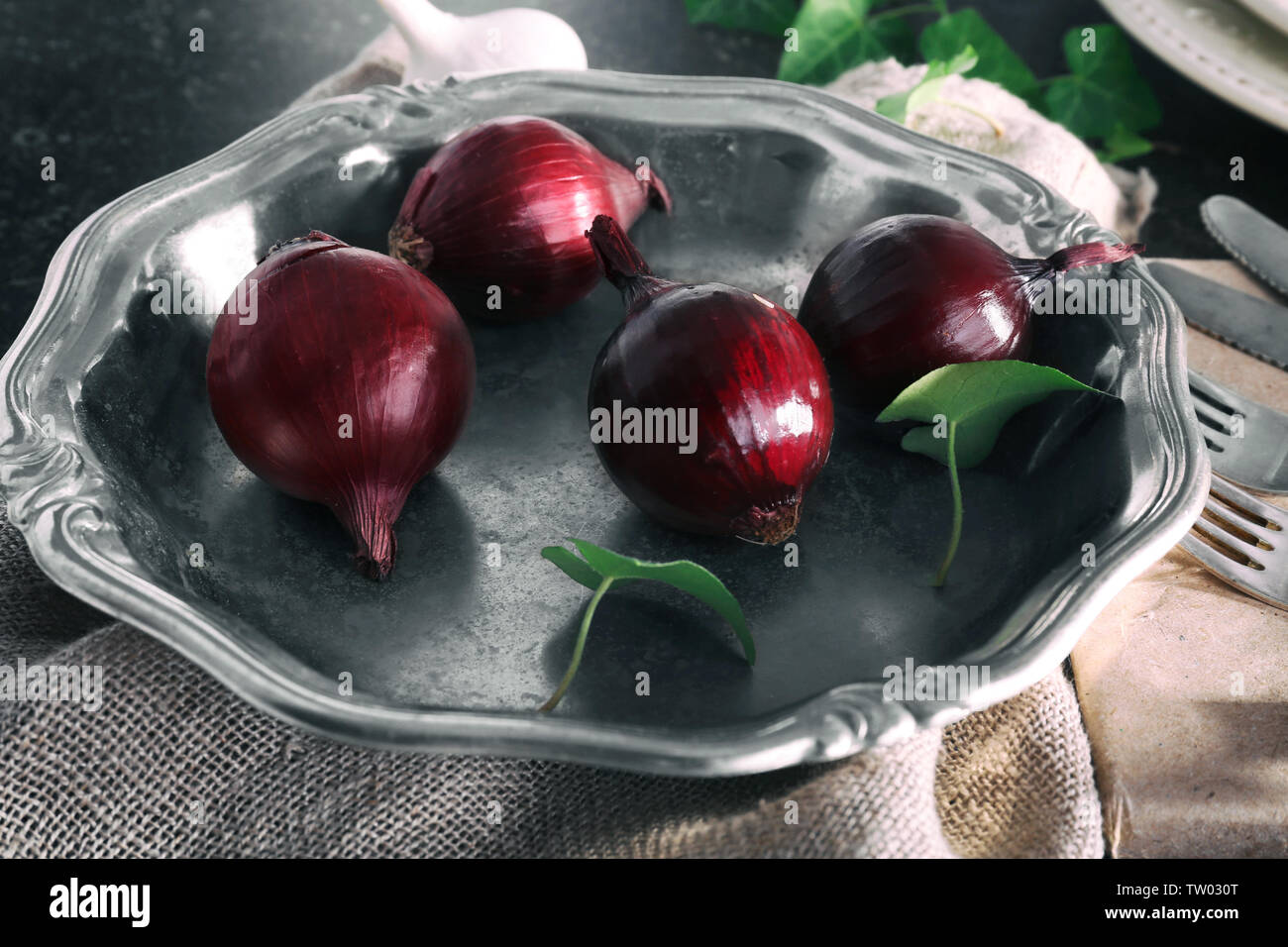 Silver bowl with red onion on gray table, closeup - Stock Image