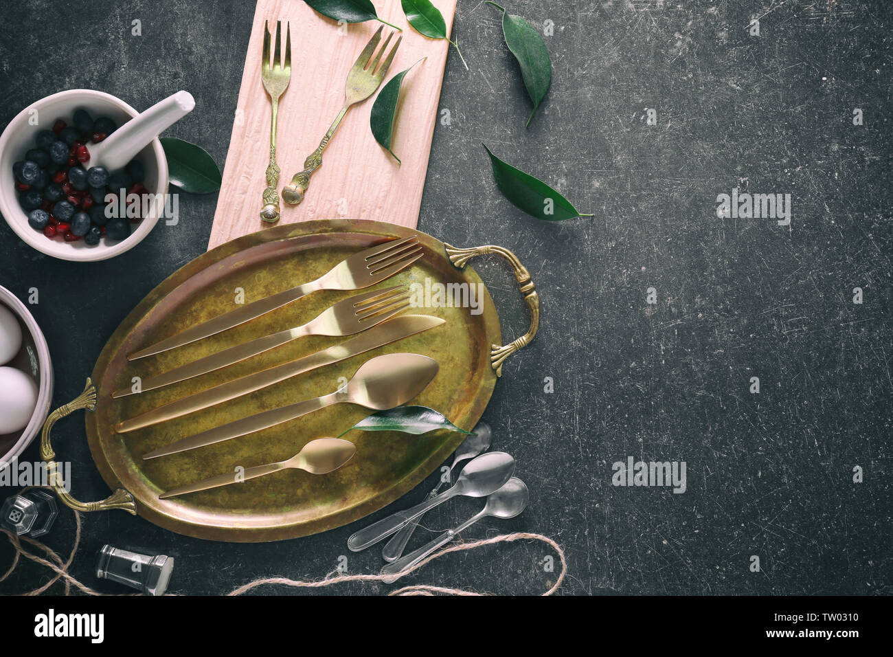 Cutlery set with copper tray, on gray background - Stock Image