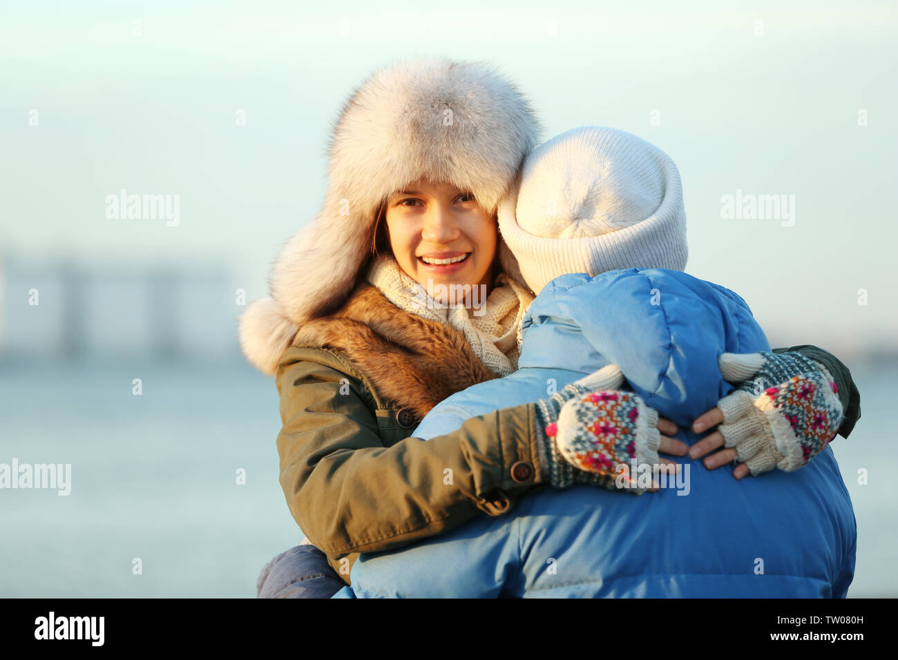 Young couple embracing on blurred river background - Stock Image