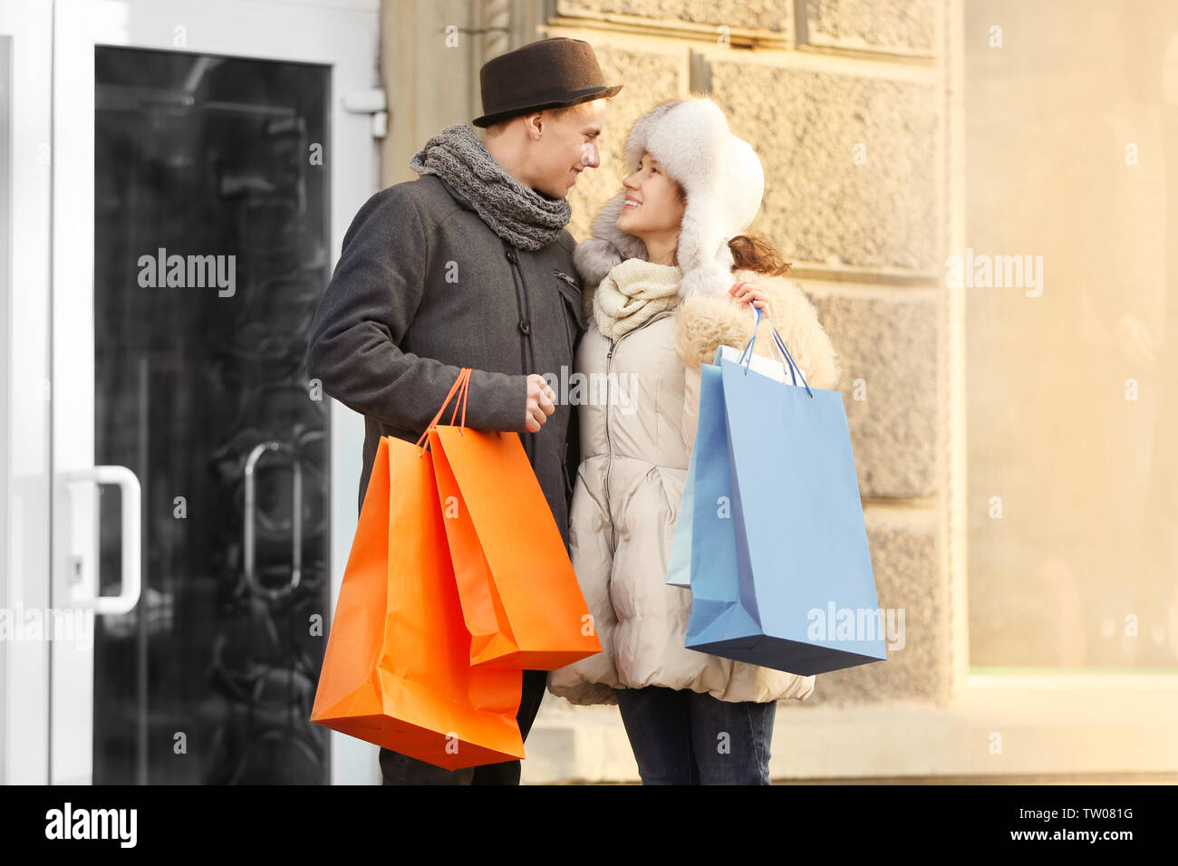 Young couple with colourful shopping bags on the street - Stock Image