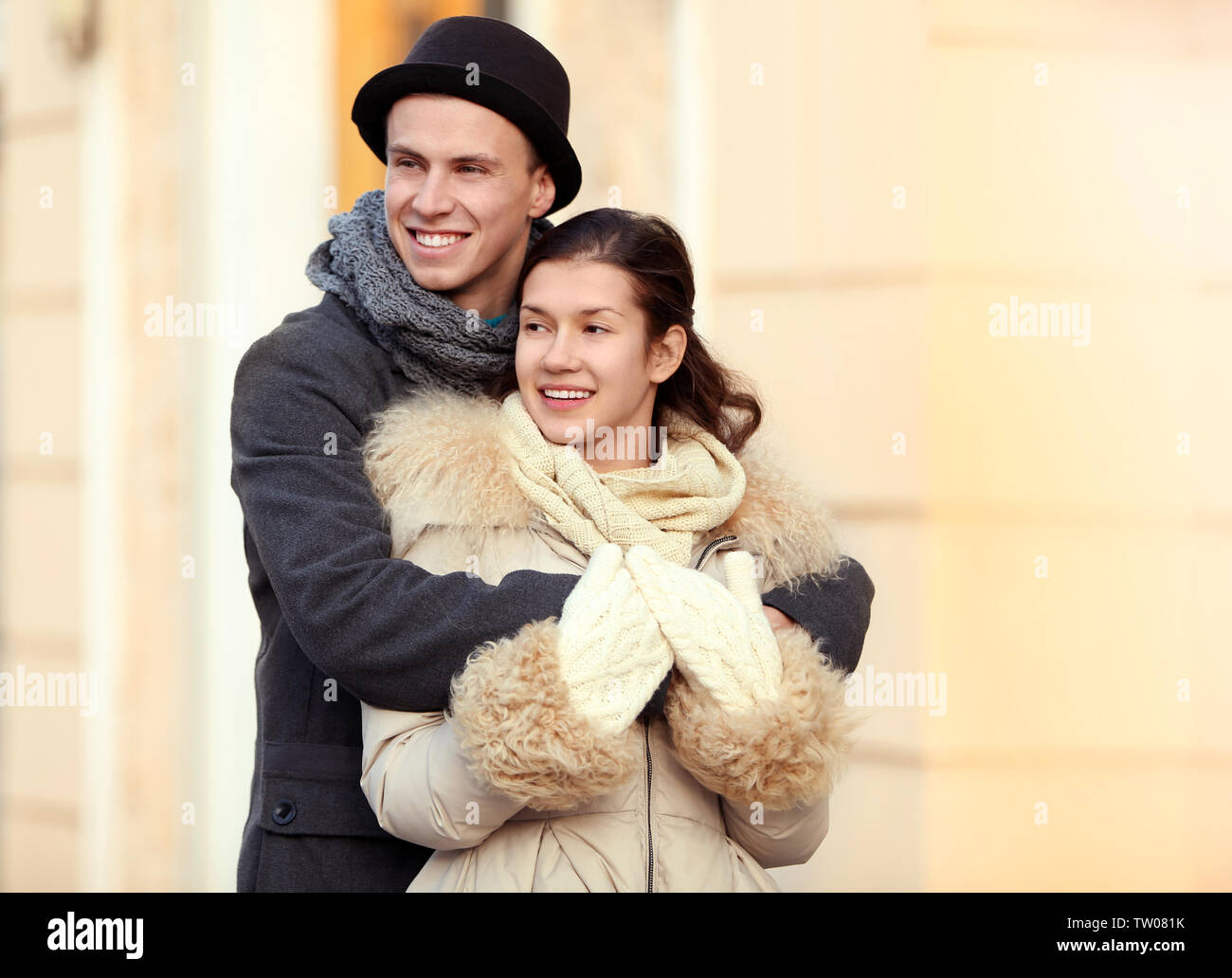Young couple embracing on the street - Stock Image