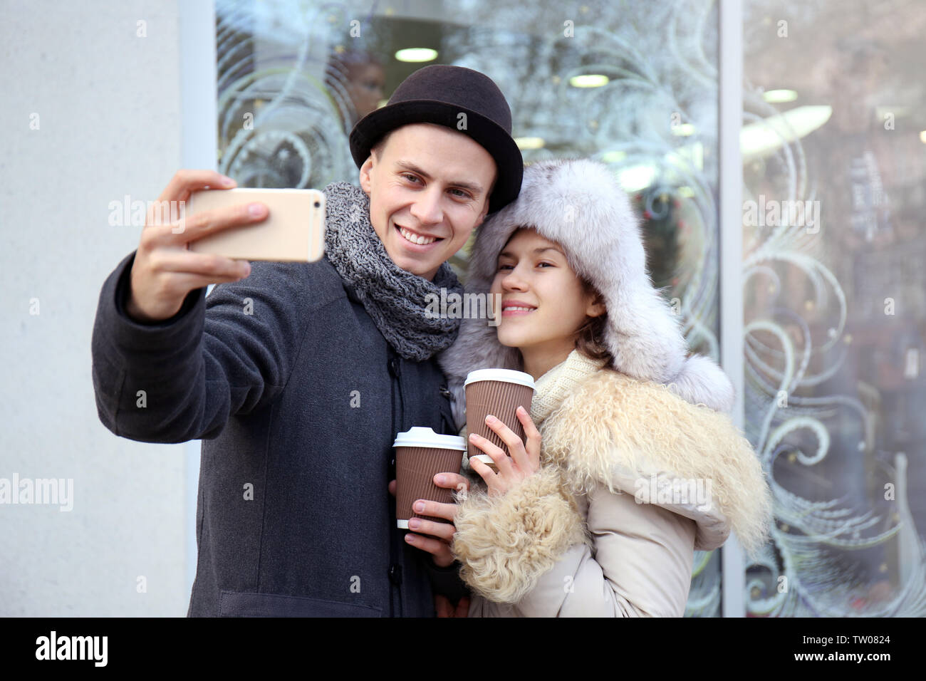 Young couple taking selfie on the street - Stock Image