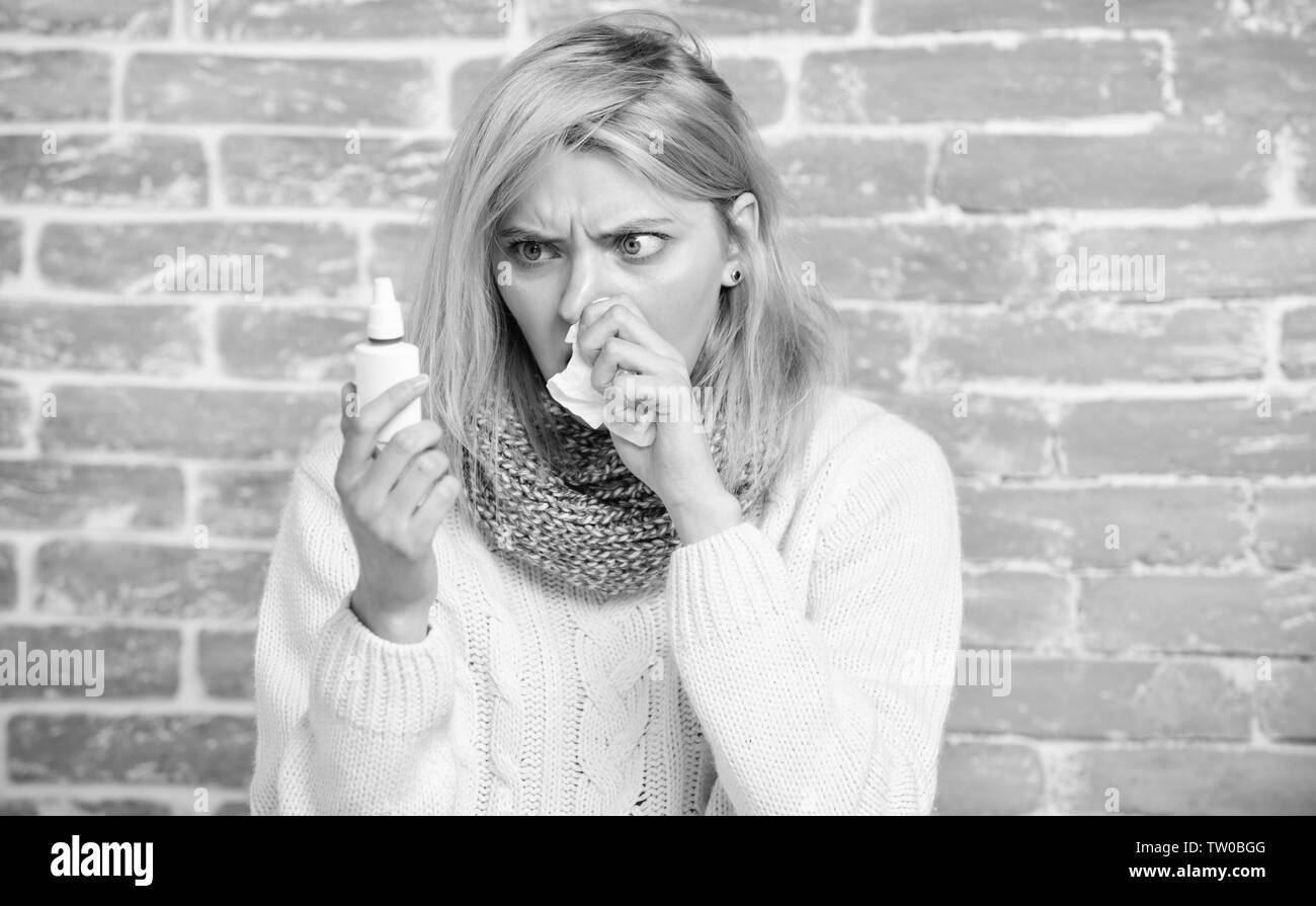 Keeping the medication in her nose. Suffering from asthma or allergic rhinitis. Sick woman with nose drops. Pretty girl with runny nose holding nasal drops. Cute woman nursing nasal cold or allergy. Stock Photo