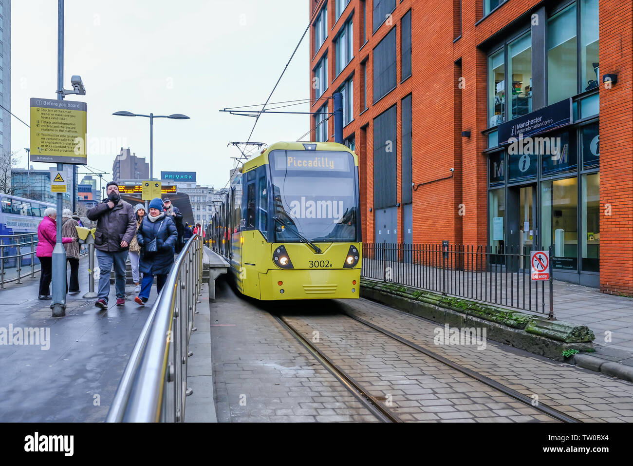 Picadilly, Manchester, UK - January 19, 2019: Yellow tram at the Picadilly stop wiht passengers leaving the station. - Stock Image