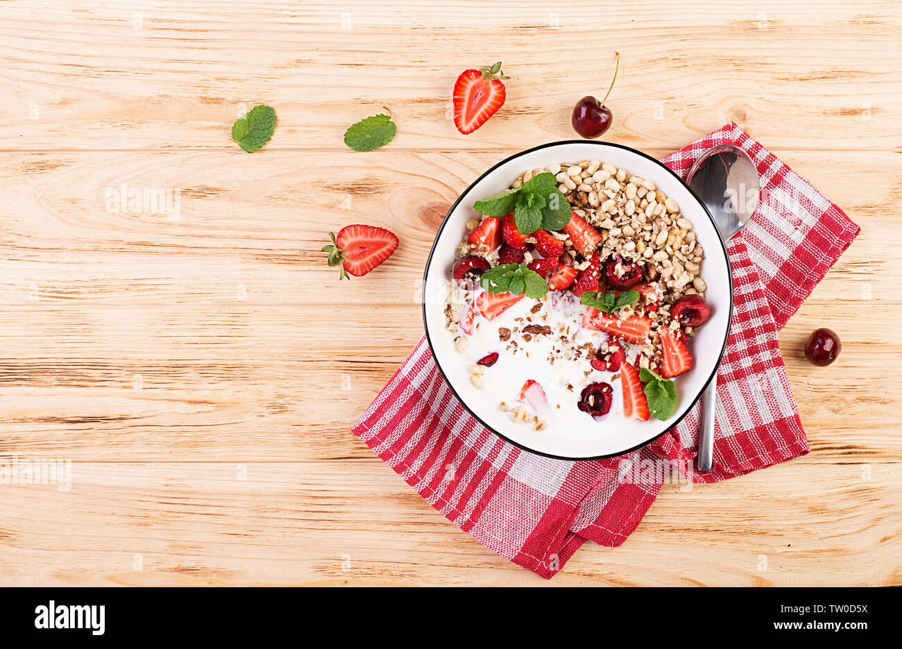 Healthy breakfast - granola, strawberries, cherry, nuts and yogurt in a bowl on a wooden table. Vegetarian concept food. Top view Stock Photo