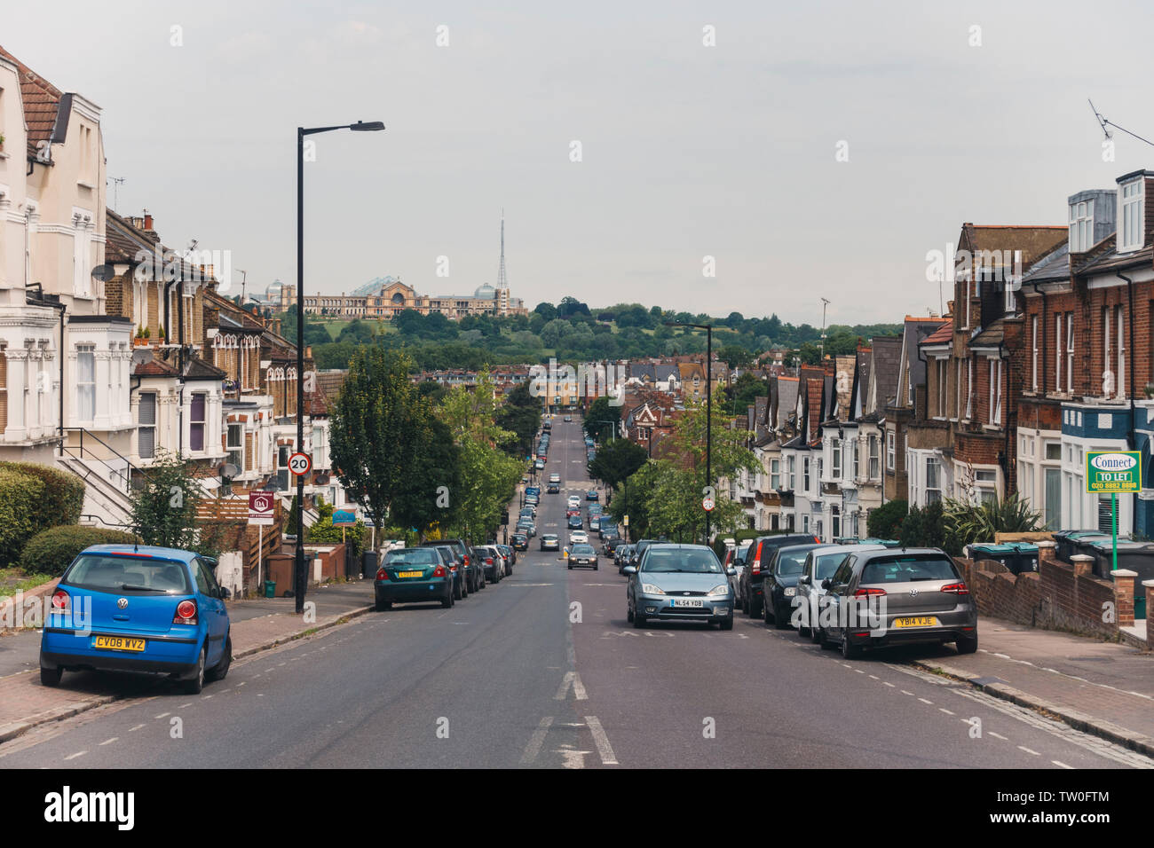 Looking down a terrace-housed residential street toward Alexandra Palace in Crouch End, North London - Stock Image
