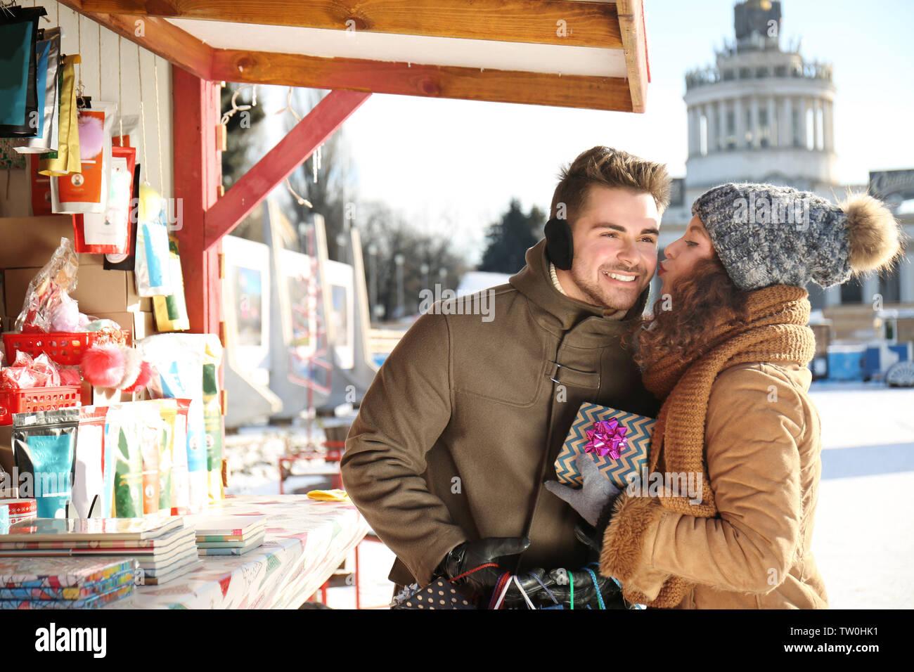 Man presenting gift to woman on Christmas market - Stock Image