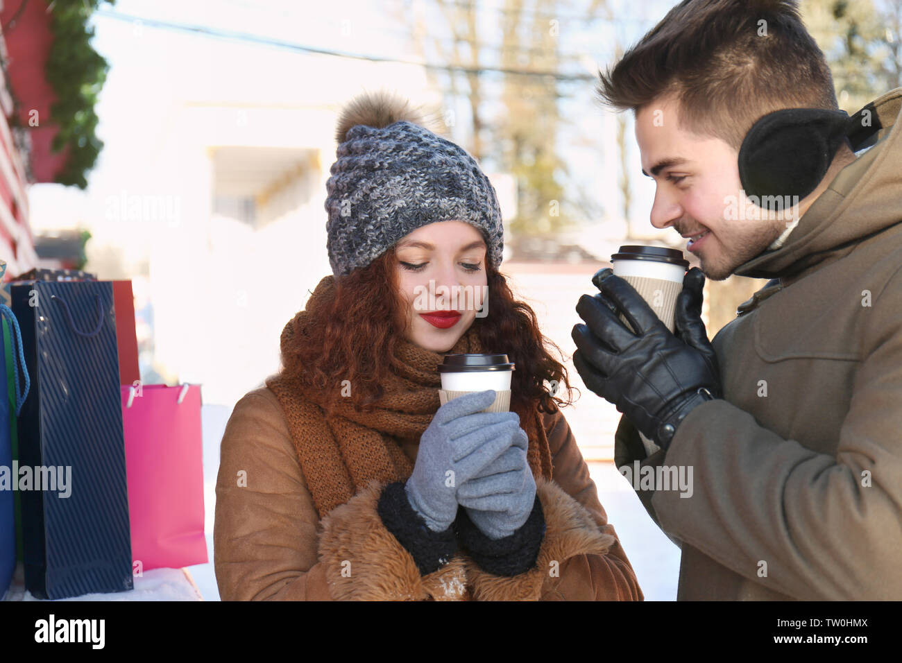 Woman and man drinking coffee on Christmas market - Stock Image