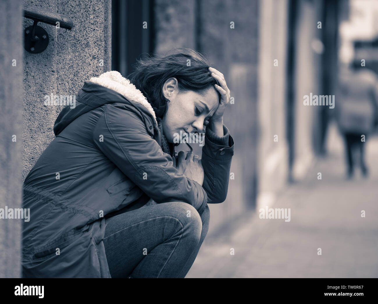 Attractive woman suffering from depression felling sad unhappy heartbroken and lonely sitting in city urban street in Mental health Emotional pain Abu - Stock Image