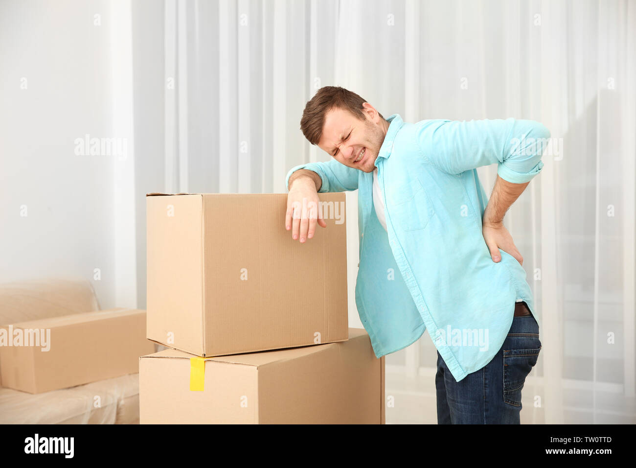 Young man suffering from pain after moving heavy box - Stock Image