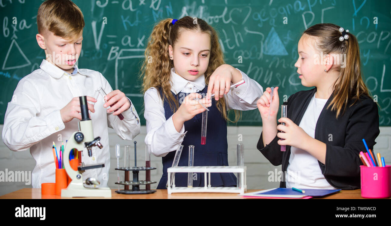 students doing experiments with microscope. Happy children. Chemistry lesson. Little kids learning chemistry in school lab. Chemistry education. Chemistry equipment. This is what we are testing today. - Stock Image
