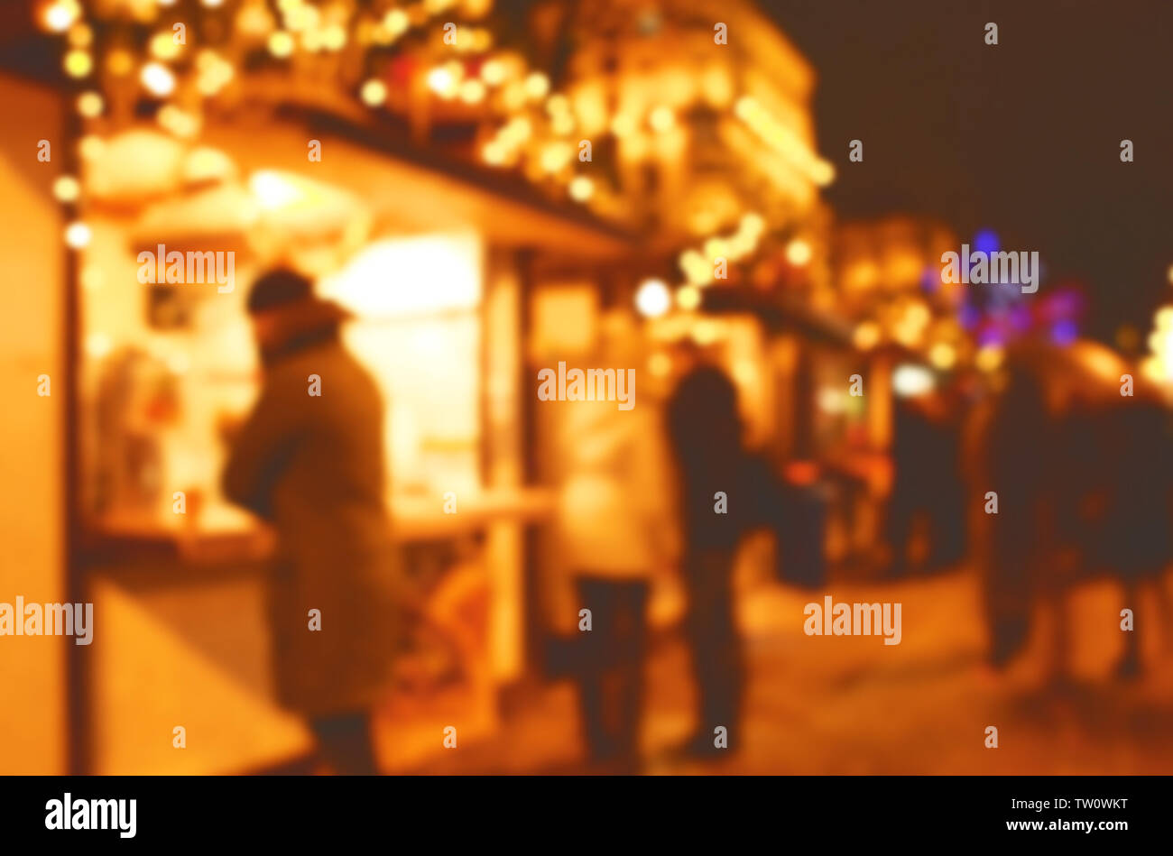 Blurred view of people on street at Christmas fair - Stock Image