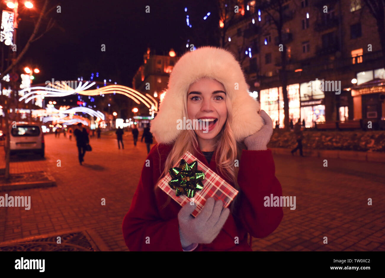 Woman with gift box on Christmas market - Stock Image