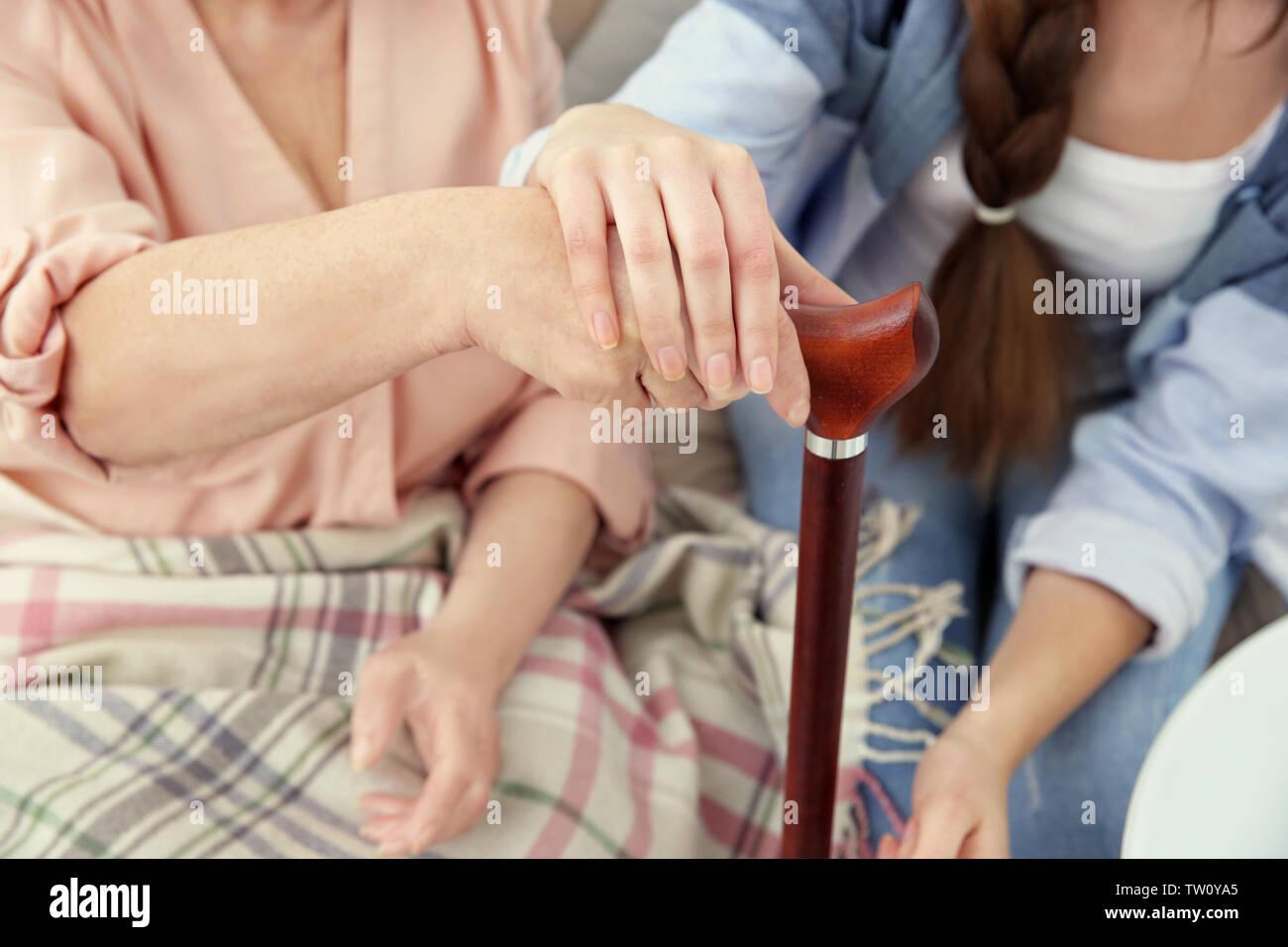 Female hands on walking stick closeup - Stock Image