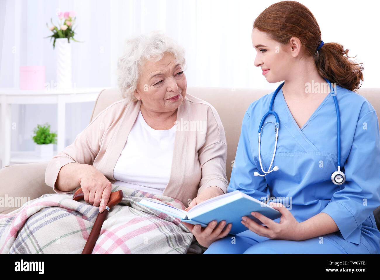Nurse reading book to elderly woman on couch - Stock Image