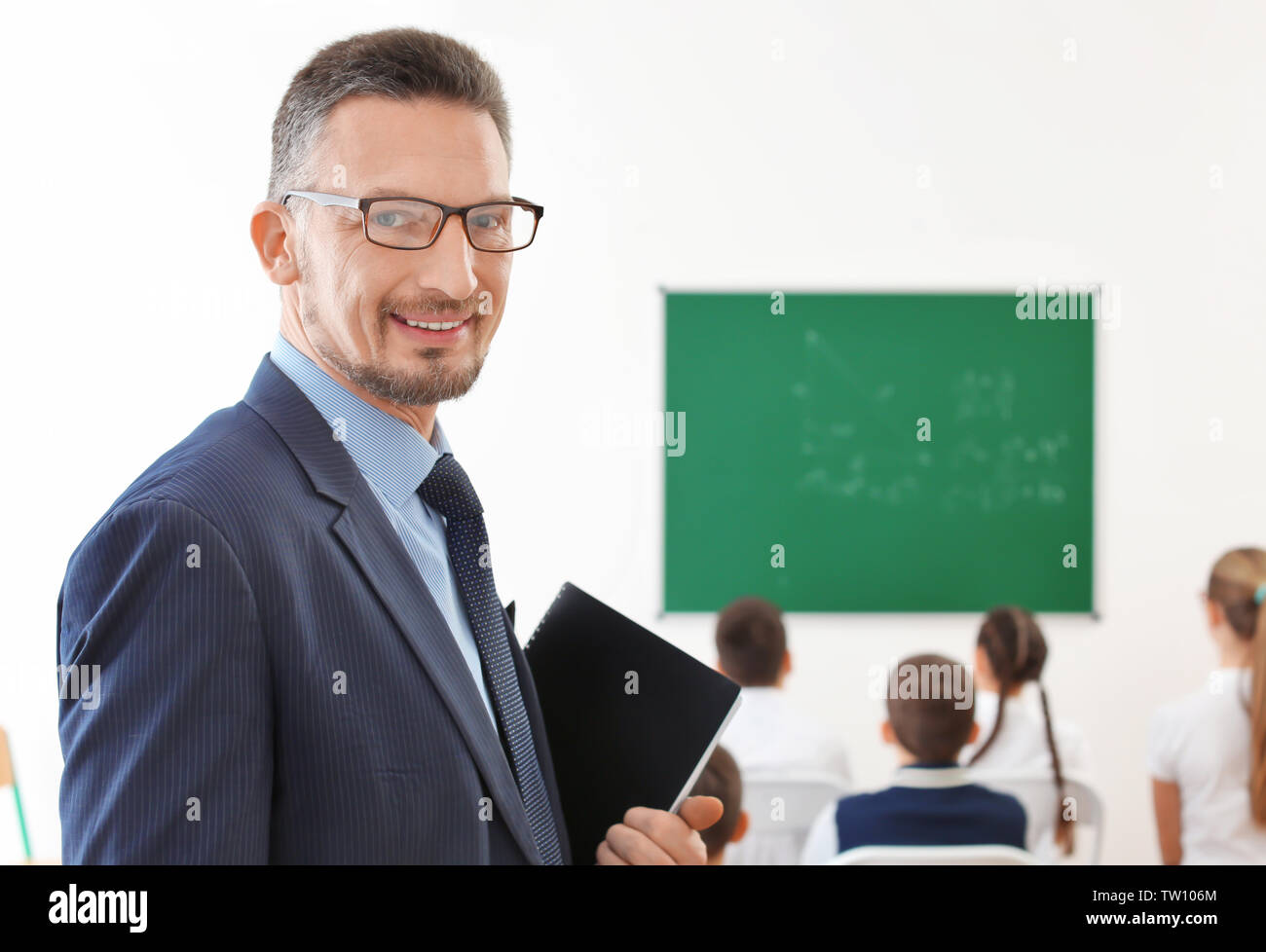 Handsome teacher with notepads in classroom - Stock Image