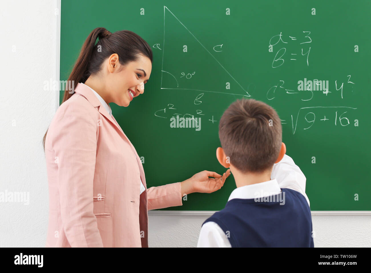 Teacher and schoolboy writing on blackboard in classroom - Stock Image