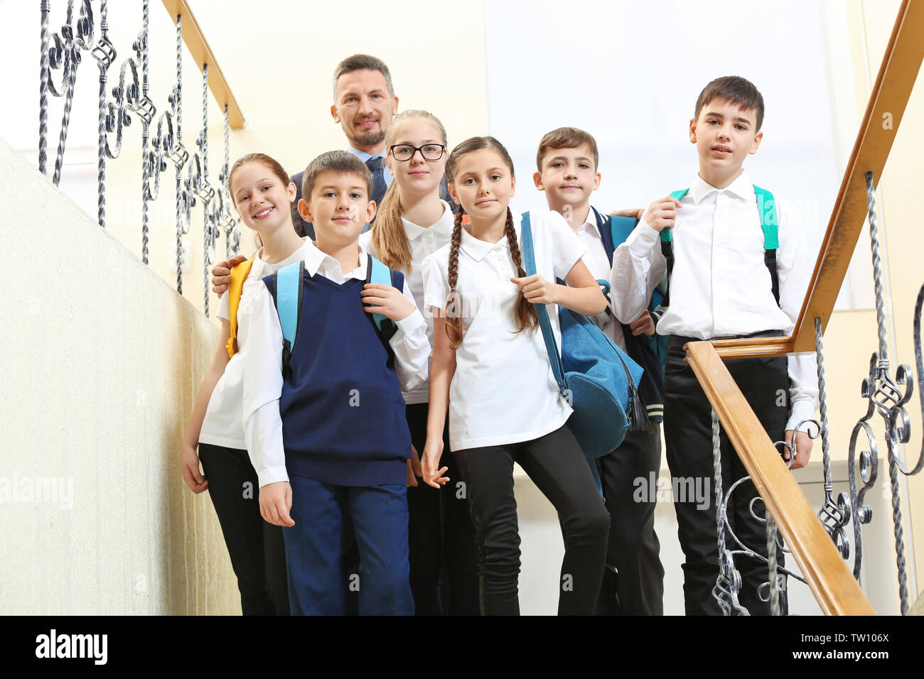 Teacher with children in school corridor during class break - Stock Image