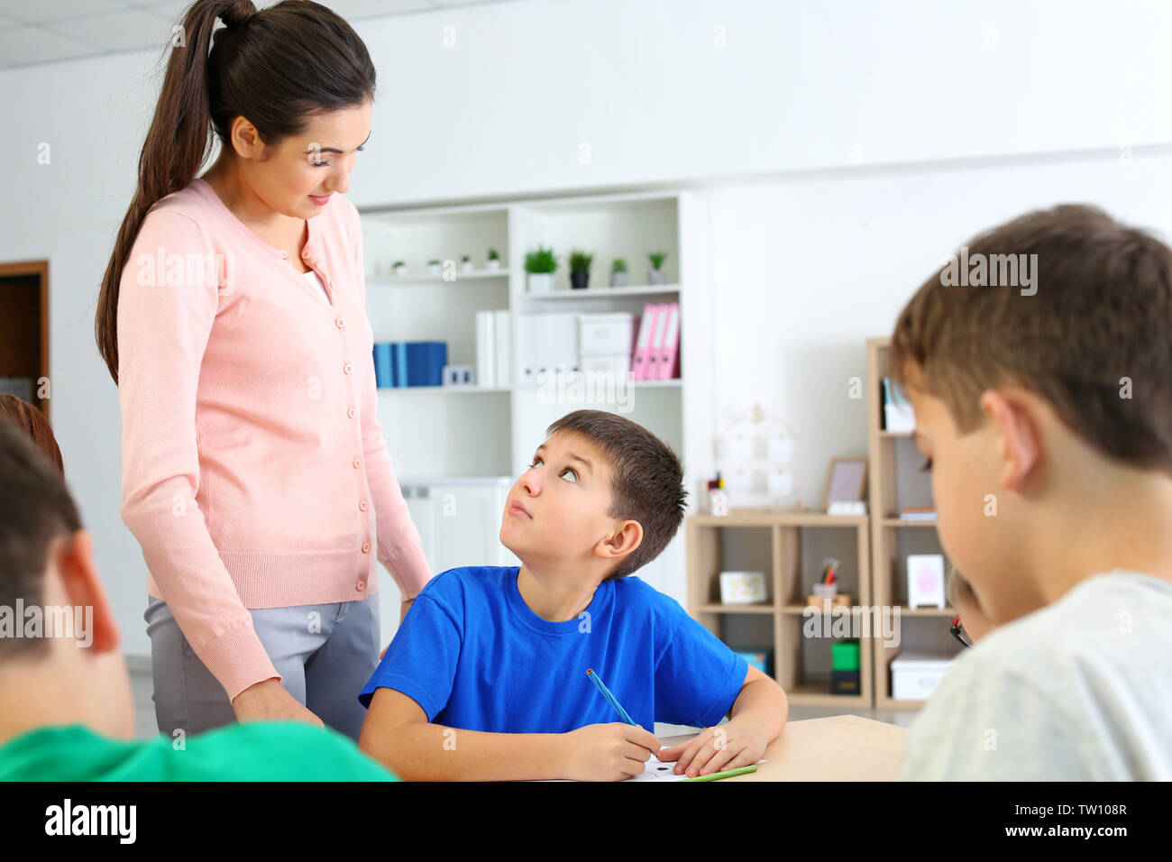 Female teacher conducting lesson in classroom - Stock Image