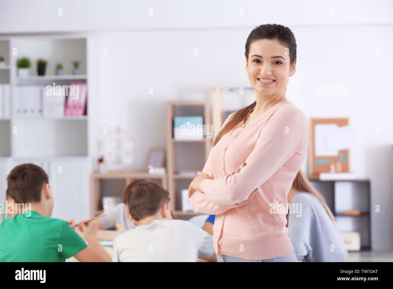 Beautiful teacher in classroom during lesson - Stock Image