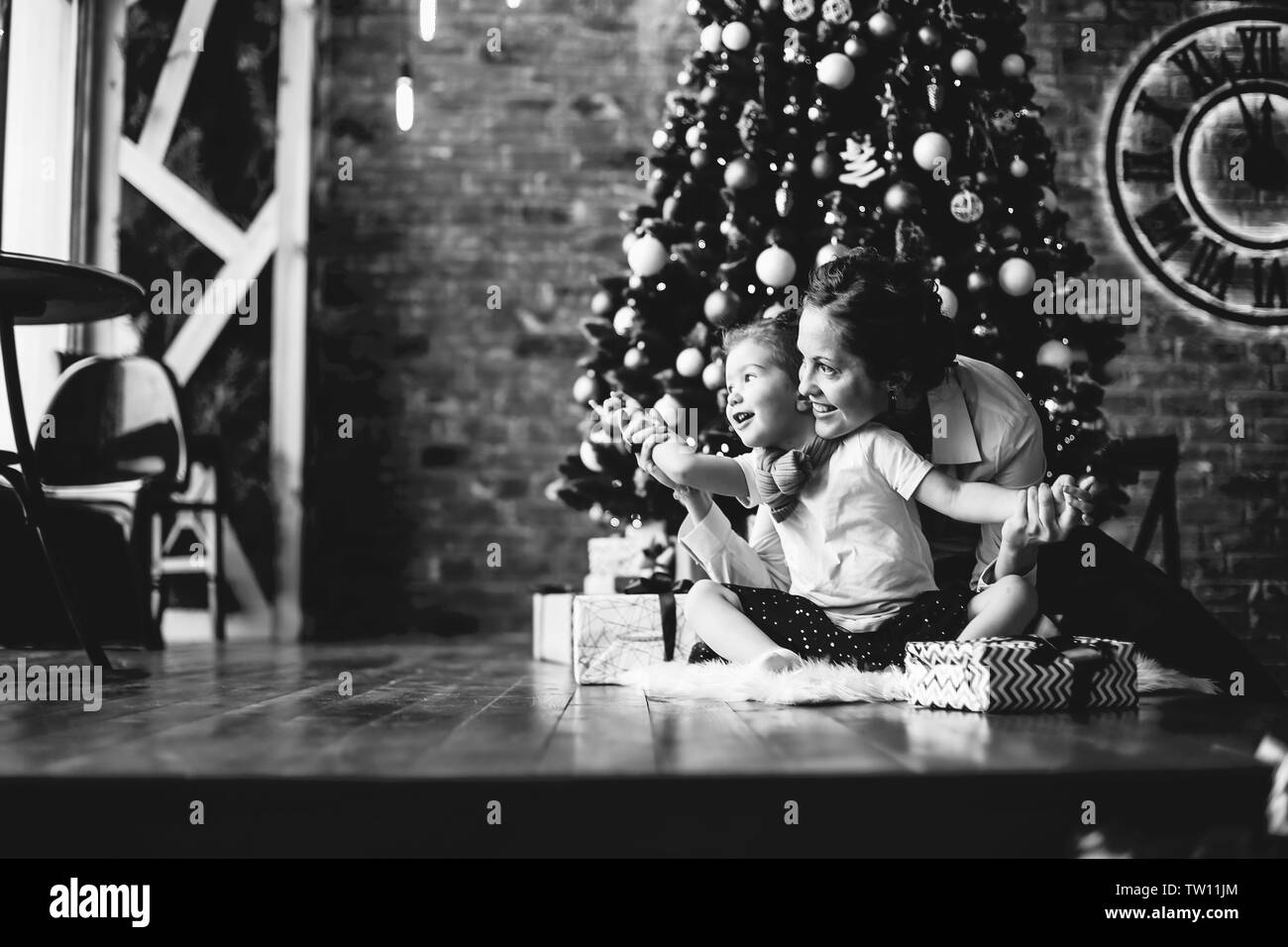 mom plays with her daughter, sitting near the Christmas tree . the concept of Christmas - Stock Image