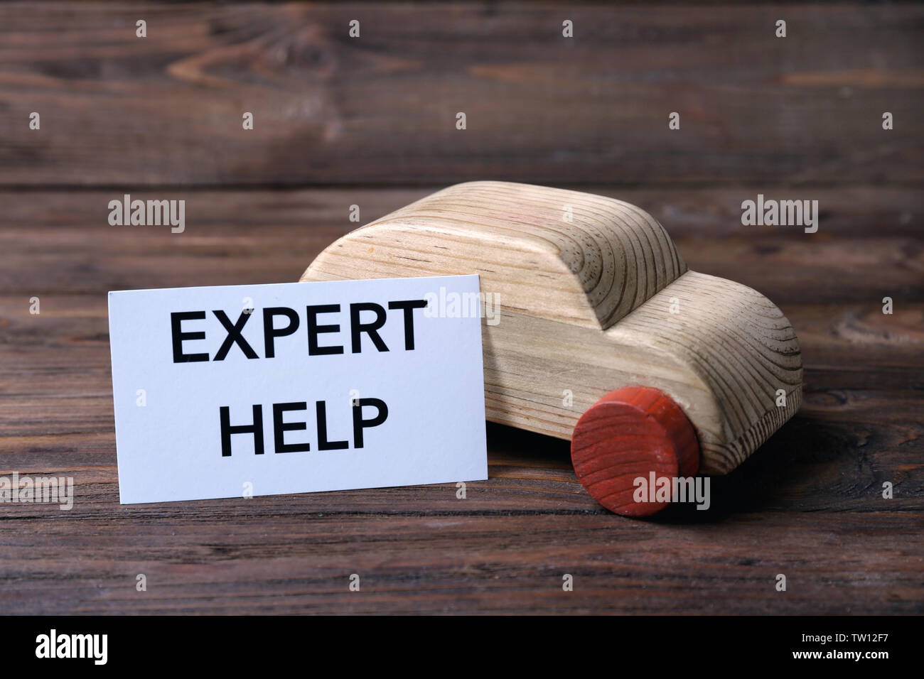 Wooden toy car and paper with phrase EXPERT HELP on wooden background - Stock Image