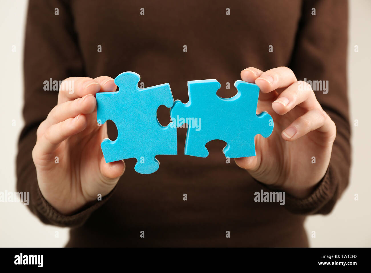 Closeup of two puzzles in female hands - Stock Image