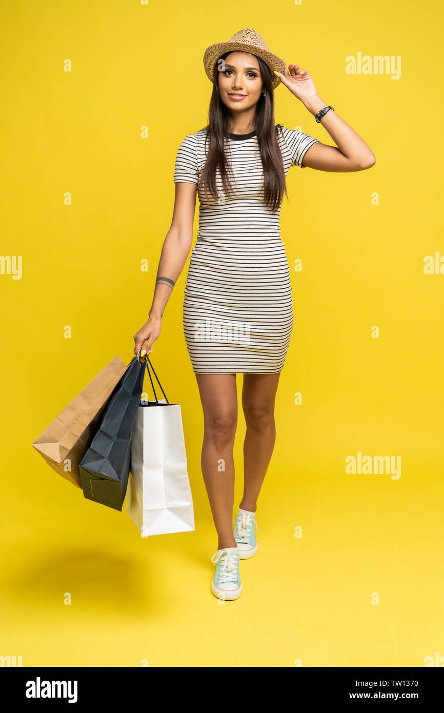 Full length portrait of a happy pretty girl holding shopping bags while walking and looking at camera isolated over color background - Stock Image
