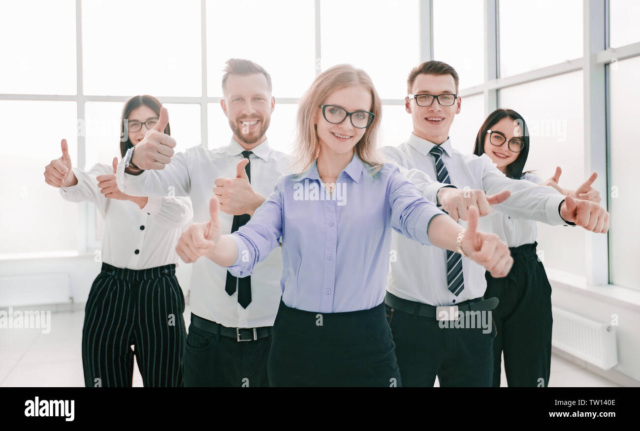 happy business team showing their thumbs up. concept of success - Stock Image