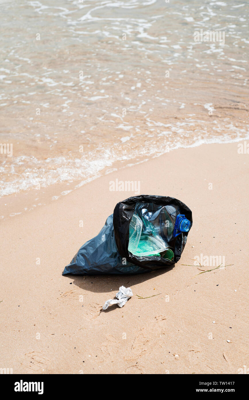 closeup of a gray plastic bag with collected garbage on the sand of a lonely beach, next to the water, in the background Stock Photo