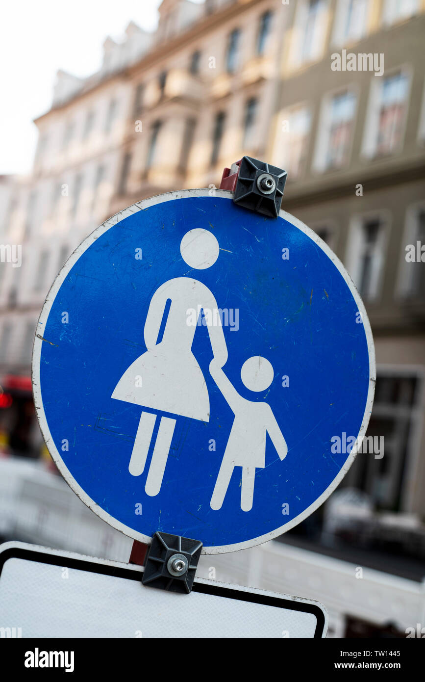 closeup of a pedestrian zone traffic sign in Germany, depicted by the silhouette of an adult holding the hand of a children, in white over a blue back - Stock Image