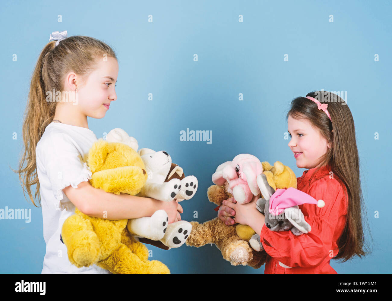 Relaxing together. playground in kindergarten. little sisters girls playing game in playroom. small girls with soft bear toys. happy childhood. handmade. sewing and diy crafts. toy shop. children day. - Stock Image