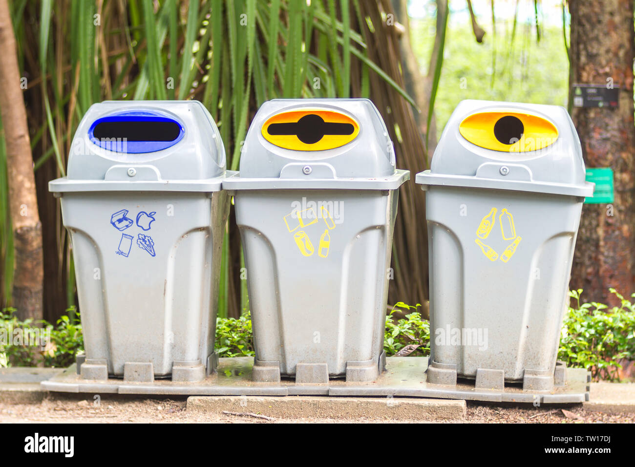 Recycle bins with recycle symbol in park Stock Photo