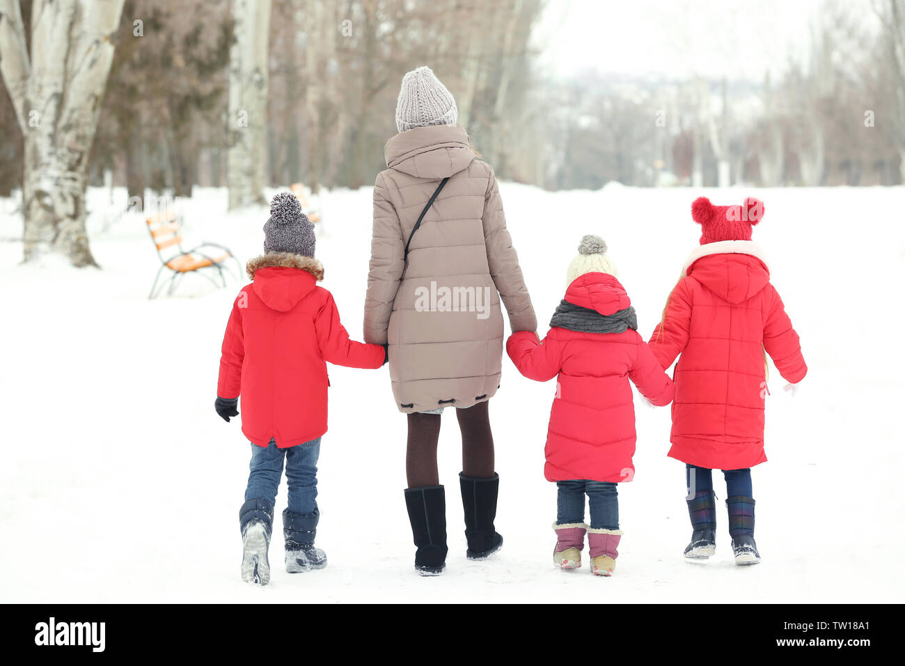 Young woman with children walking on snow - Stock Image