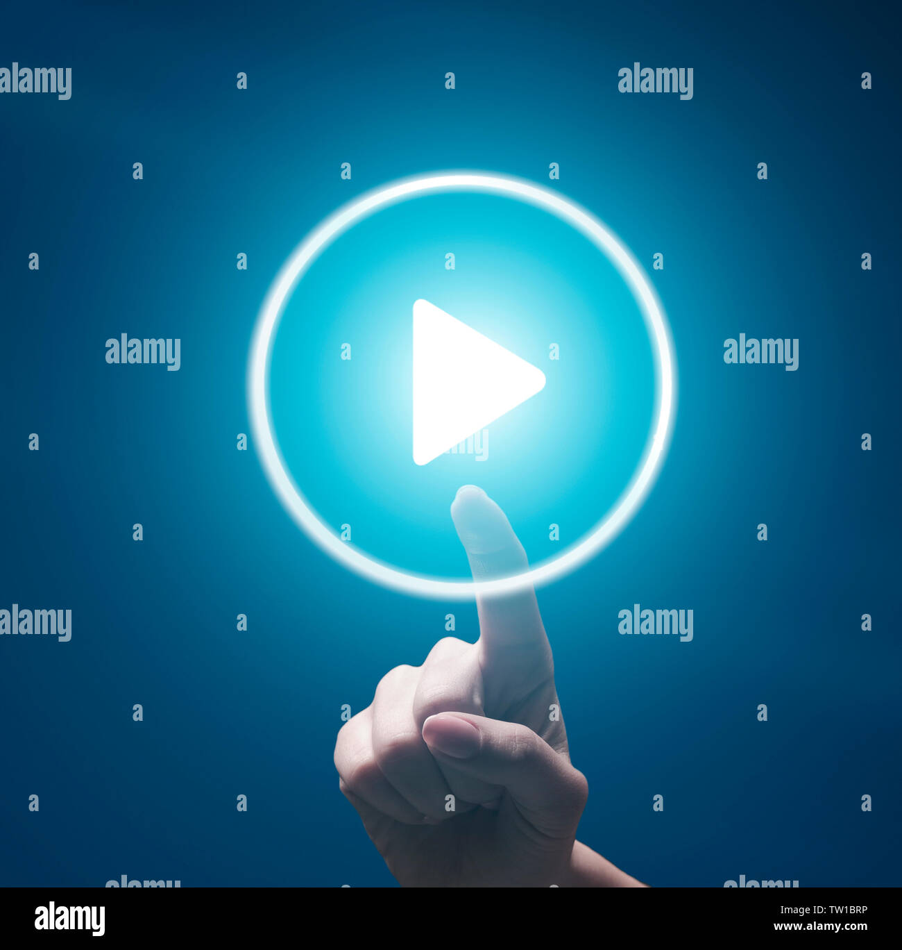 Female finger pushing transparent Play button on blue background - Stock Image