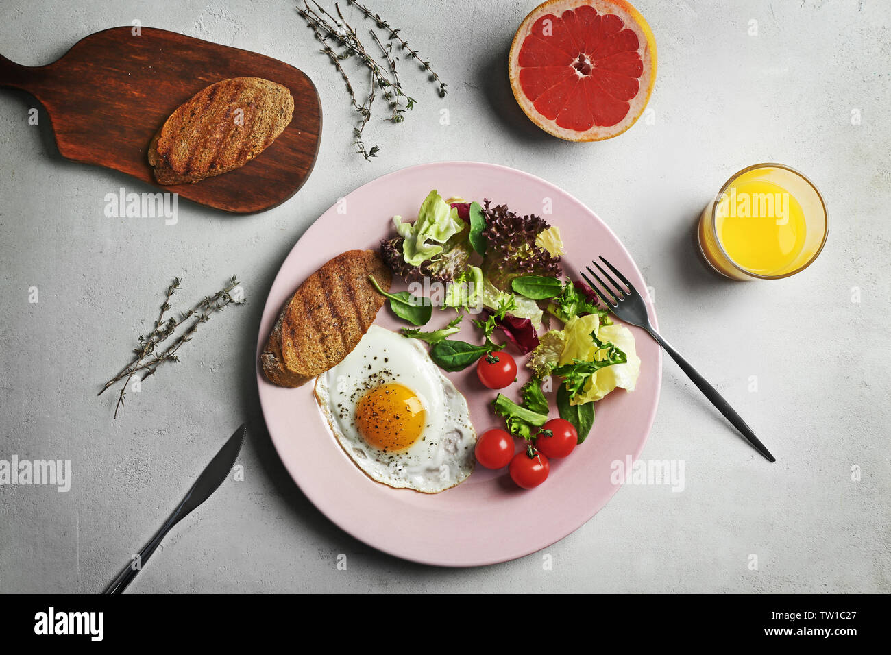 Tasty breakfast with egg and juice on gray background Stock Photo