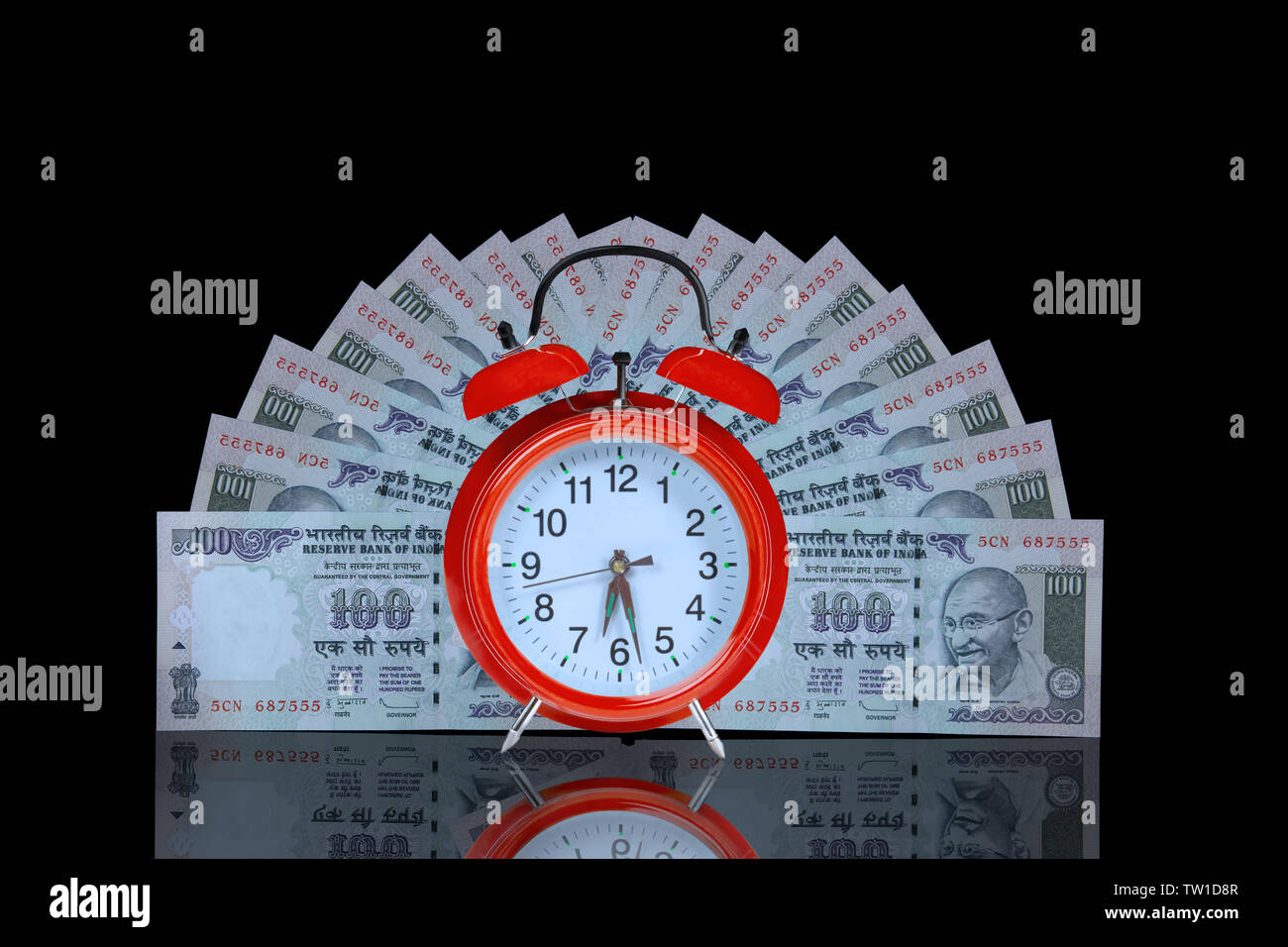 Alarm clock with hundred rupee banknotes Stock Photo