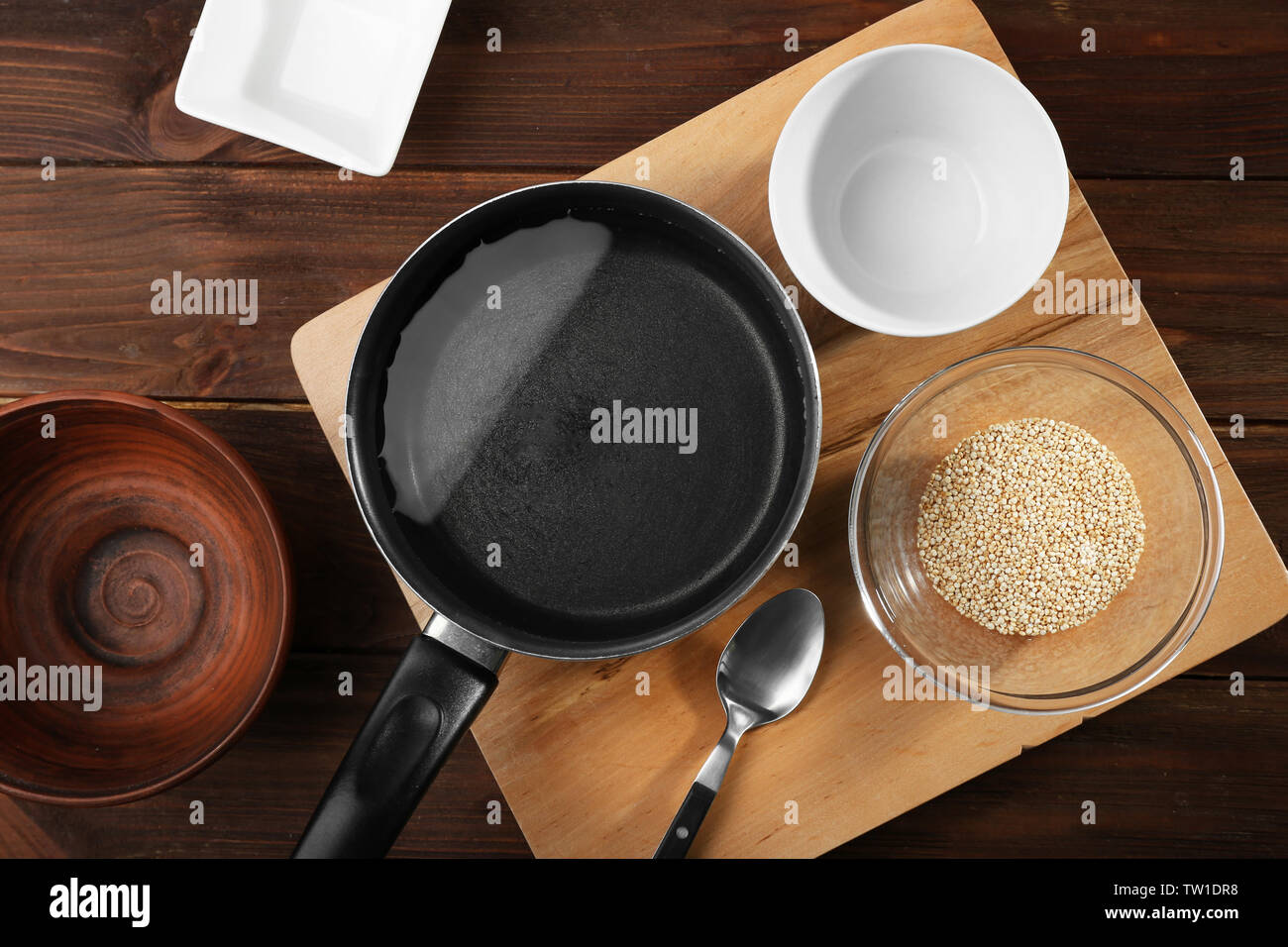 Kitchen utensils and quinoa seeds in bowl on wooden table - Stock Image