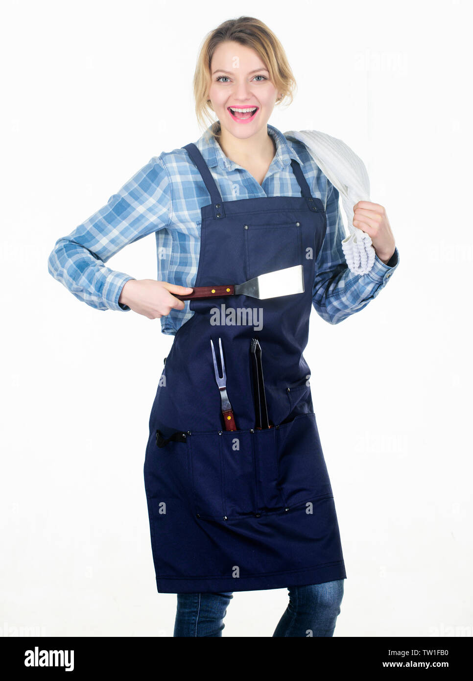 Need some help. Picnic barbecue. food cooking recipe. Pretty girl in chef apron. Preparation and culinary. Tools for roasting meat outdoor. Woman hold kitchen utensils. Family weekend. - Stock Image