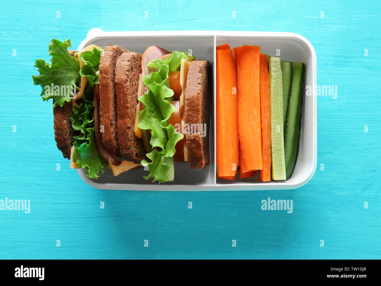 Healthy school lunch in plastic box on blue wooden table Stock Photo