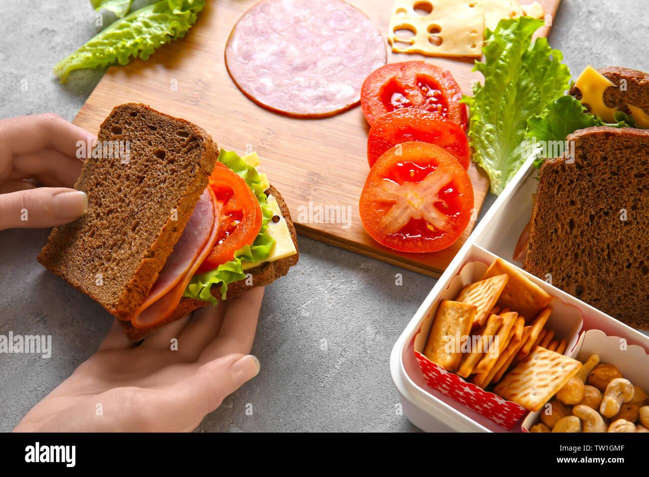 Woman making tasty sandwich on table Stock Photo