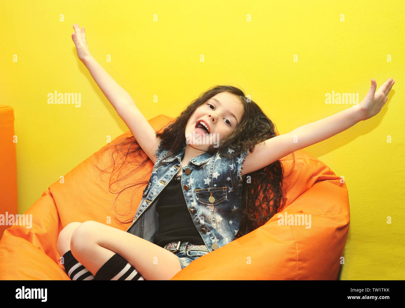 Beautiful small girl in frameless chair - Stock Image