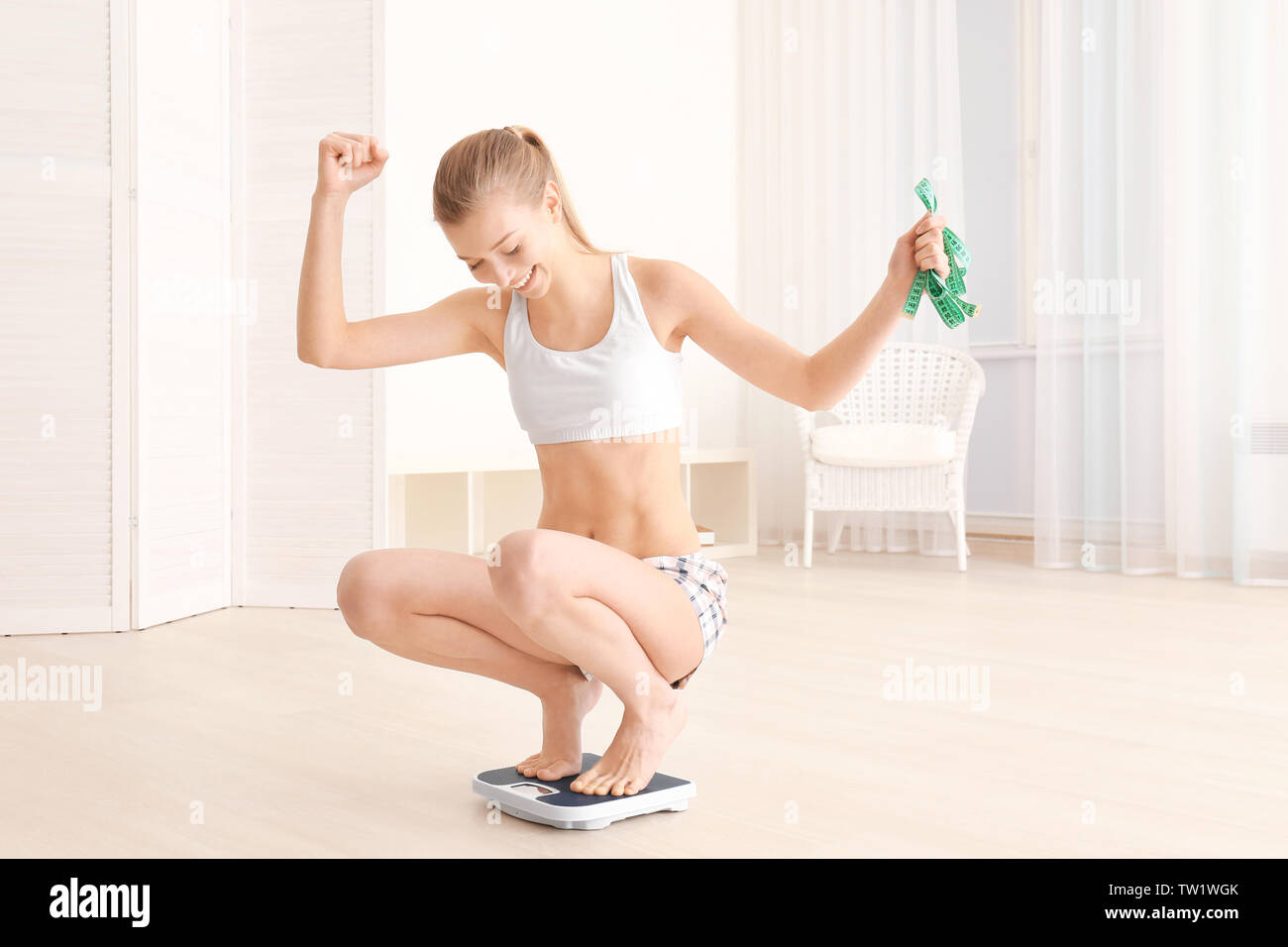 Diet concept. Young beautiful woman sitting on scales Stock Photo