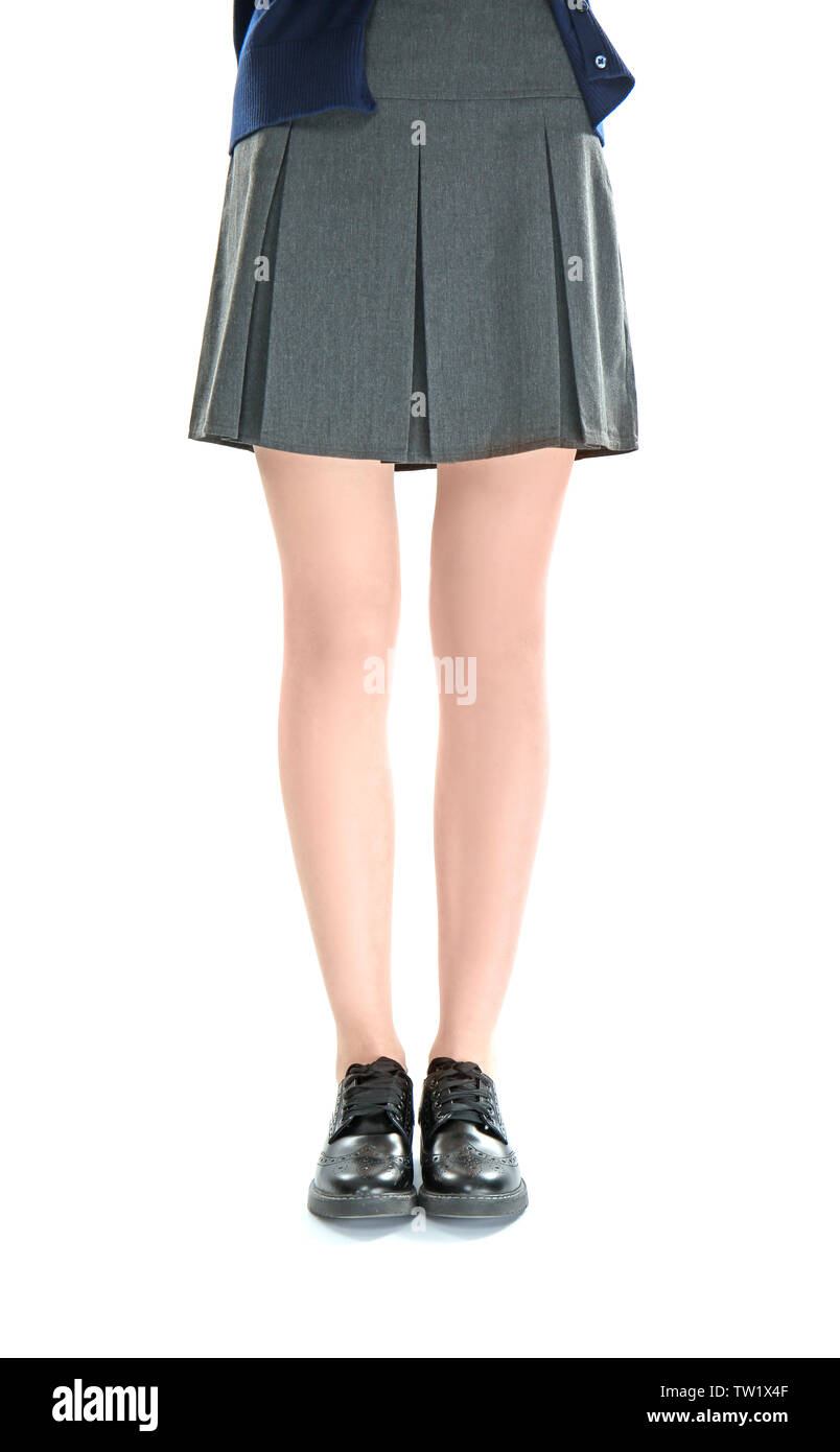 aab3ffdf06 Slender schoolgirl legs in black skirt and leather shoes on white background  - Stock Image