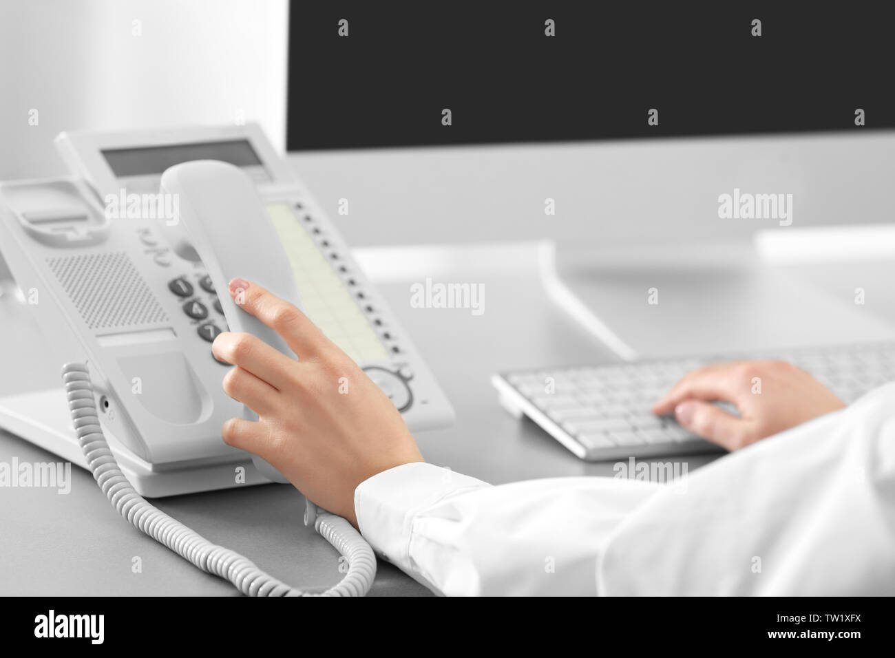 Woman dialing number on telephone while working in office - Stock Image