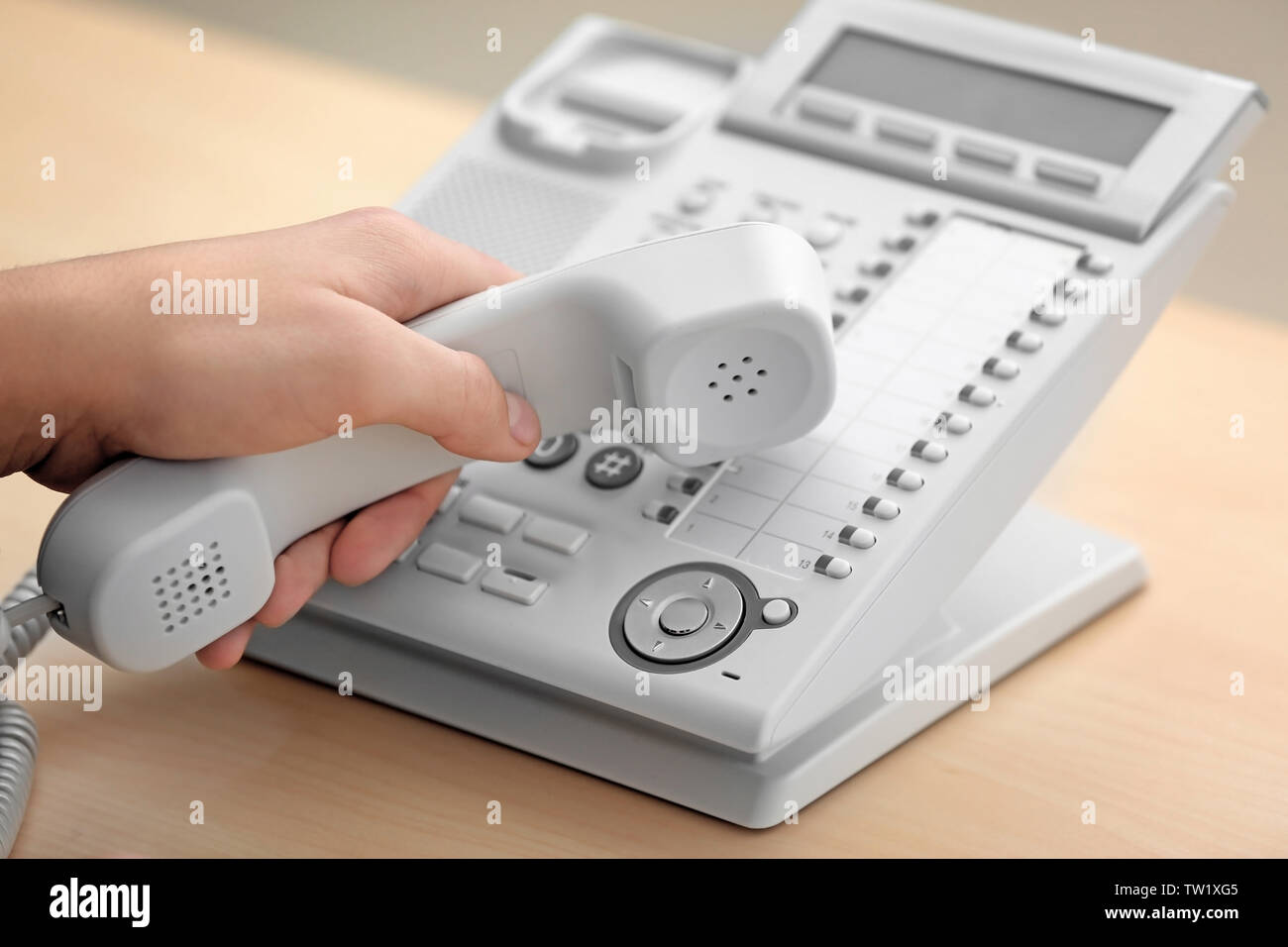 Hand of man with picked up receiver dialing telephone number in office - Stock Image