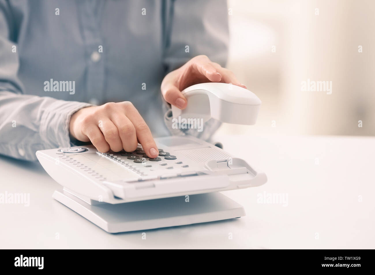 Woman dialing telephone number in office - Stock Image